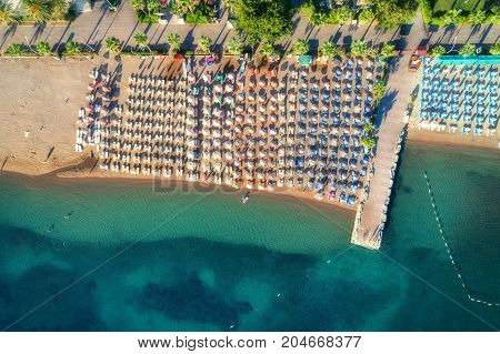 Aerial view of transparent turquoise sea, beautiful sandy beach with colorful chaise-lounges, boats, green trees at sunset in Icmeler, Turkey. Summer seascape. Top view from flying drone. Azure water