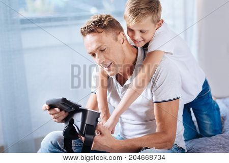 Pure affection. Gentle pre-teen boy cuddling his father from behind while the man sitting on the bed and being about to close VR headset with a phone in it