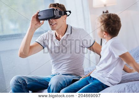 Modern technology. Pleasant pre-teen boy sitting on the bed next to his father and watching him test a VR headset while the man enjoying the process