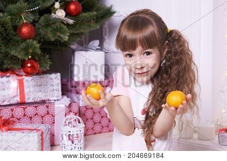 Little girl. Christmas interior. Mandarin and gifts