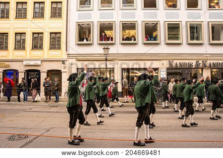MunichGermany-September 172017:Viewers wave from their windows in a fioor at one of the groups taking part in the Oktoberfest Parade