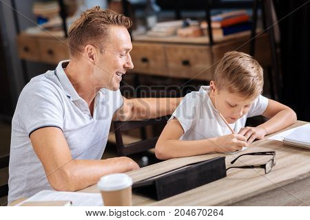 My diligent student. Happy proud father and his pre-teen son sitting at the table in the study and the man watching his son diligently write a note on a piece of paper