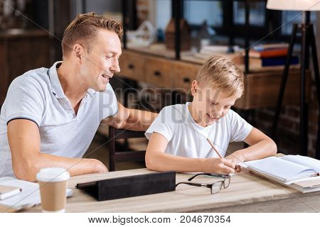Hard-working student. Charming young father sitting at the table in the study and watching his beloved son make notes on a sheet of paper