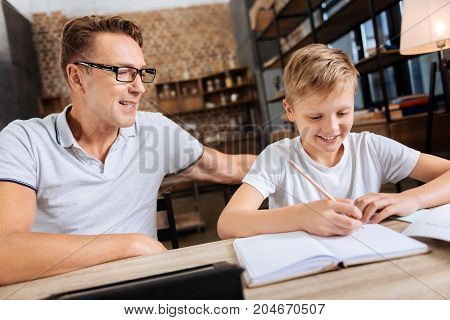 Crucial help. Cheerful pre-teen boy sitting next to his father in the study and doing his home assignment in the notebook while the man supervising him, ready to help