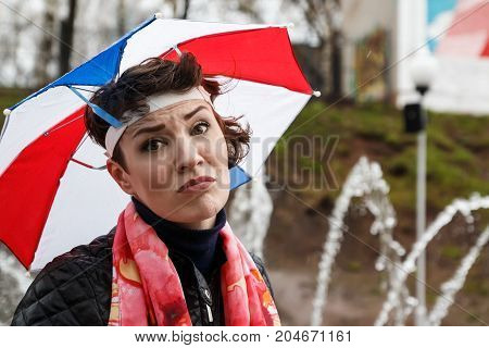 Emotional Girl With Colorful Umbrella On Her Head In The Park