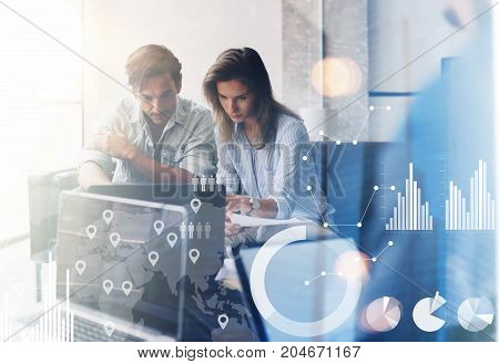 Concept of digital diagram, graph interfaces, virtual screen, connections icon.Two young coworkers working on computer at sunny office.Woman pointing on notebook screen. Blurred background