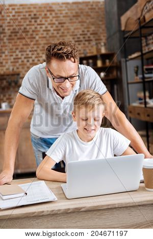 Careful supervision. Pleasant young father standing behind his pre-teen son and watching him work on laptop in the study, being ready to provide any help needed