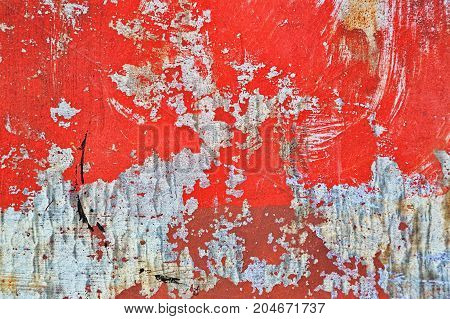 Metal plate background with rough texture and numerous traces of use weather effects corrosion. Old red paint is almost erased.