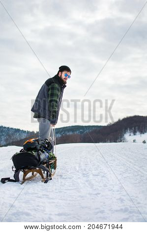 Man Puling Sleights Up Snowy Mountain