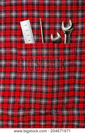 Repairman tools - wrenches screwdriver and ruler tool in checkered work shirt pocket. Craftsman classic outfit.