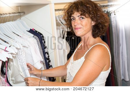 Half Body Shot  Woman Looking At Clothes Hanging On The Rail Inside The Clothing Shop