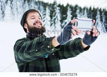 Bearded Man Taking Selfie On The Snowy Mountain