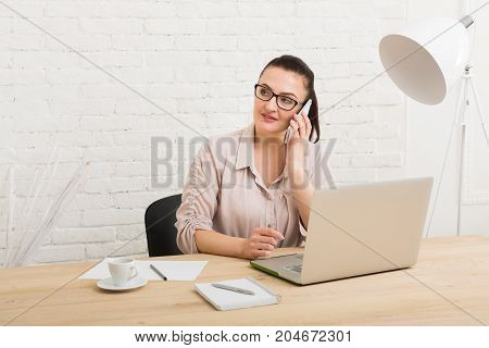 Middle-aged business woman in office with smartphone. Female using laptop computer and talking on mobile phone at workplace, copy space. Communication concept
