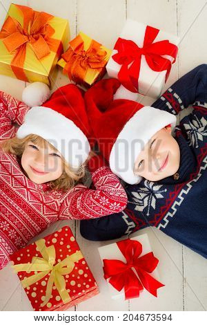 Portrait of happy children with Christmas gift boxes. Two kids having fun at home