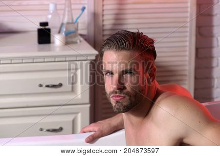 Guy In Bathroom With Toiletries On Background.
