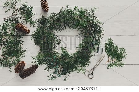 Christmas handmade diy wreath and garland. Creative craft hobby. Home leisure, tools for holiday decorations. Top view of white wooden table