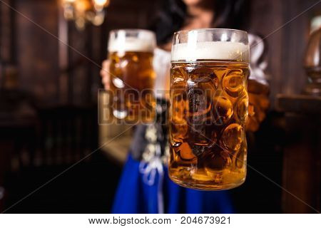 Young sexy Oktoberfest waitress, wearing a traditional Bavarian dress, serving big beer mugs at bar. Focus on two glasses of beer