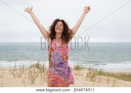 Portrait Of Young Female Walking On The Sea Shore Looking At Camera Laughing. Woman Strolling Along