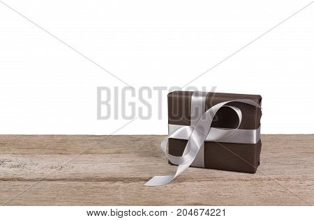 Gift box wrapped with brown paper and silver satin ribbon on wooden table at white background. Modern presents for any holiday, christmas, valentine or birthday