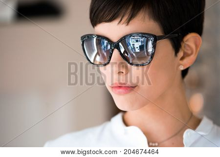 Young beautiful woman at optician with glasses buying fashion sunglasses