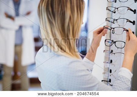 Pretty young woman is choosing new glasses at optics store to correct eyesight