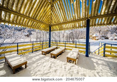 A wooden gazebo in a park in the snow and clear blue sky