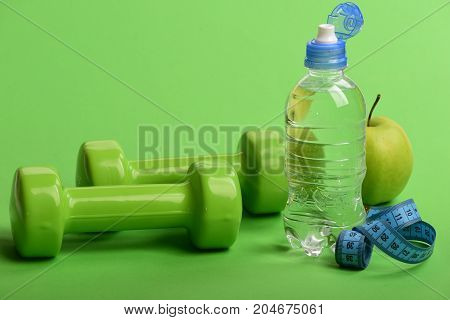 Dumbbells In Green Color, Water Bottle, Measure Tape And Fruit