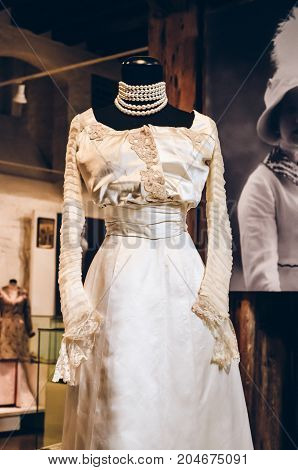 Riga, Latvia - July 5, 2012 - Part of lovely tulle and velvet ball qown with machine made lace applique. Florence, 1903-1904. Romantic dress champagne color for wedding ideas, design. Closely view.