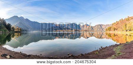 Panorama of active volcano Baru Jari Lake Segara Anak and summit of Rinjani mountain. Lombok island Indonesia.