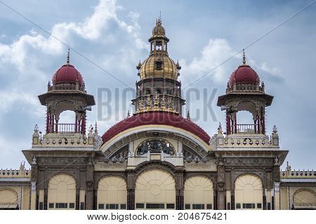 Mysore India - October 27 2013: Closeup of front entrance with maroon domes to Mysore palace with the central tower with golden domes peeping above it under cloudscape.