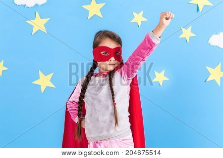 Little girl plays superhero. Kid on the background of bright blue wall with white clouds and yellow stars. Girl power concept.