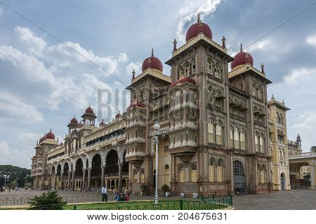 Mysore India - October 27 2013: Wide shot of East facade of Mysore Palace under cloudscape. Beige building with towers and maroon domes. Seen from Northeast corner.