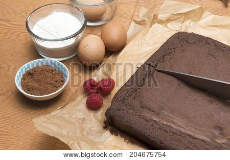 Chocolate brownie bake with flour, eggs, raspberries and coco powder