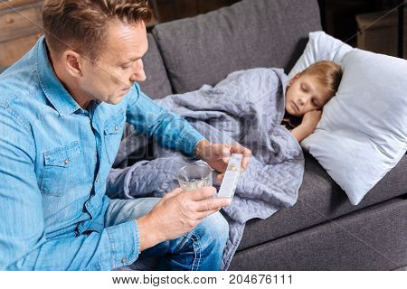 Necessary medication. Concerned young father sitting on the couch next to his ill son, holding a glass of water and an open pills organizer, being about to give a pill to the boy