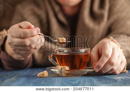 Male hands add sugar in hot tea