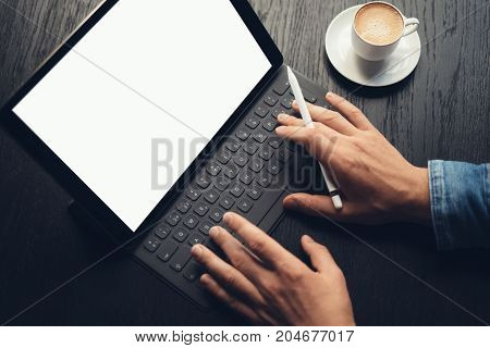 Men using tablet and typing on electronic tablet keyboard-dock station while sitting at wooden table.White blank device screen.Blurred background.Horizontal mockup