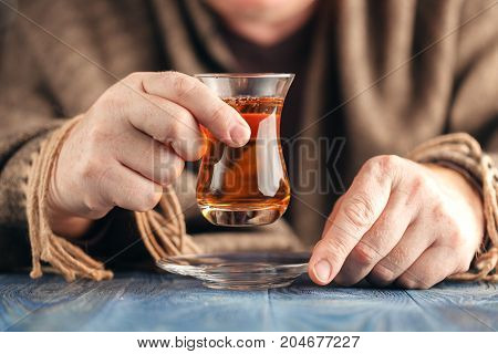 Man in sweater drink hot tea from turkish glass