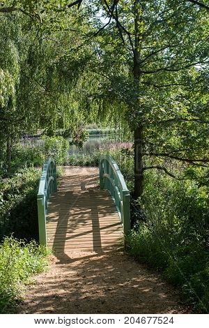 Pretty green wooden footbridge to English countryside lake in Summer ornamental gardens