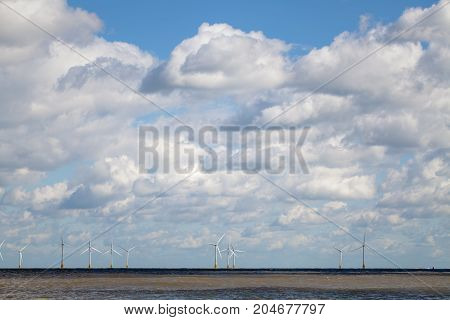 Offshore wind farm on horizon beneath cloudy sky. Weather and sustainable resources providing clean energy for the future. Beautiful seascape.