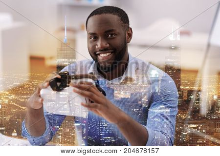 Provoking interest. Close up of optimistic young man looking at you and smiling while holding virtual glasses in hands
