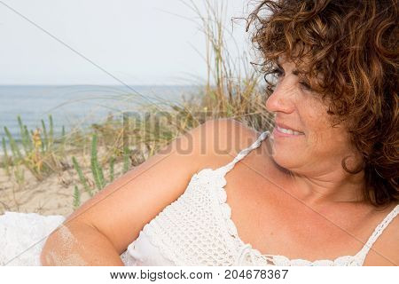Attractive And Happy Middle Aged Woman Lying Along The Seashore