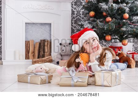 Beautiful dreamy girl unwrap christmas present box on holiday morning in beautiful room interior. Female child open Xmas gift near decorated fir tree and fireplace. Winter holidays concept
