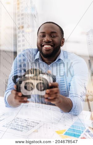 Have a look. Delighted African American holding virtual glasses in both hands and showing them to you while expressing enjoyment