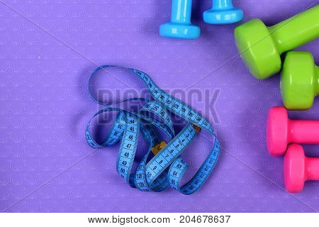 Dumbbells And Measure Tape In Cyan Color On Purple Texture