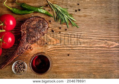 Barbecue dry aged rib of beef with vegetables and glass of red wine close-up on wooden background. Top view. Copy space. Still life. Flat lay