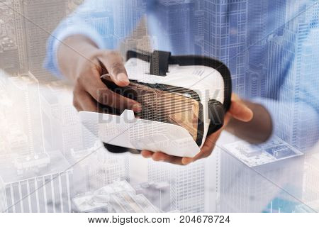 Exiting device. Close up of African American keeping virtual mask in hands and sitting at the table