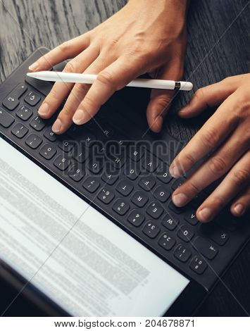 Closeup view of two male hands typing on electronic tablet keyboard-dock station. Man working at office and using electronic pen.Vertical.Cropped