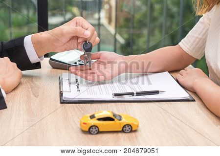 Businessman giving car key over car loan application document with car toy and calculator on wooden desk