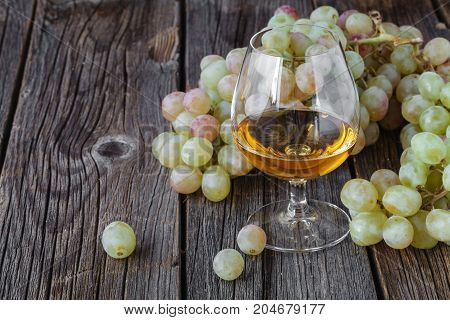 Glass Of Brandy With Brush Of Grapes On Table, Harvest Holiday