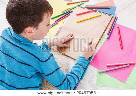 Writing letter to santa. Cute boy makes wish list of presents for christmas. Drawing picture. Prepare for winter holidays, top view of child on floor